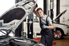 An attractive young car mechanic is smiling: car service and maintenance royalty free stock photos