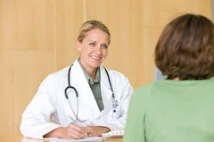Attractive young caring doctor Stock Images