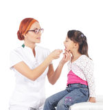 A happy female doctor inspecting a little brunette girl Stock Photos