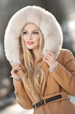 Attractive young Caucasian adult with light brown fur coat hood. Beautiful blonde girl with gorgeous eyes wearing fur, outdoors Stock Photo