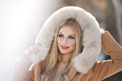 Attractive young Caucasian adult with light brown fur coat hood. Beautiful blonde girl with gorgeous eyes wearing fur, outdoors Stock Photography