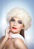 Attractive young Caucasian adult with white scarf isolated on grey background. Beautiful girl with red lips in white fur hat Royalty Free Stock Images