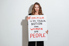 Attractive young caucasian lady holding blank with text about feminism. Royalty Free Stock Image