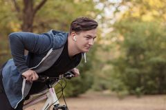 Young handsome caucasian man bicycling at the park royalty free stock image