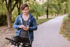 Handsome caucasia man with round eyeglass and earphones bicycling in the park stock photo