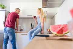 Young caucasian man washing up dishes, while his girlfriend who is sitting on kitchen counter, holds glass of red wine Stock Photos