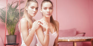Beautiful caucasian twins female models on pink background. Royalty Free Stock Photos