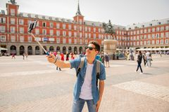 Handsome young caucasian tourist man happy and excited taking a selfie in Plaza Mayor, Madrid Spain. Attractive young caucasian tourist student man having fun Stock Image