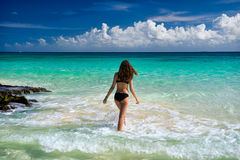 Attractive young caucasian woman in black swimsuit looking on se. A at tropical beach Stock Photos