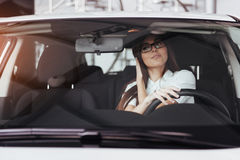 Attractive young Caucasian woman. Looking at the camera from the front seat of the car Stock Images