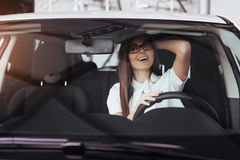 Attractive young Caucasian woman. Looking at the camera from the front seat of the car Stock Photo