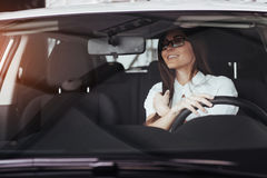 Attractive young Caucasian woman. Looking at the camera from the front seat of the car Royalty Free Stock Image