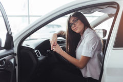 Attractive young Caucasian woman. Looking at the camera from the front seat of the car Stock Photography