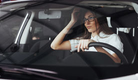 Attractive young Caucasian woman. Looking at the camera from the front seat of the car Royalty Free Stock Images