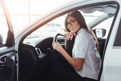 Attractive young Caucasian woman. Looking at the camera from the front seat of the car Royalty Free Stock Photography