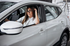 Attractive young Caucasian woman. Looking at the camera from the front seat of the car Royalty Free Stock Photo