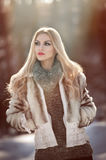 Attractive young Caucasian woman with short fur jacket in winter park. Beautiful blonde girl with gorgeous eyes and long hair Royalty Free Stock Photography