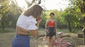 Attractive young caucasian woman with short hair posing with her bicycle while her friend taking a photo in the garden. Attractive young caucasian woman with stock video