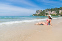 Attractive Young Caucasian Woman In Swimsuit Sitting On Beach, Girl Wear Hat Blue Sea Water Holiday. Summer Vacation Royalty Free Stock Photos
