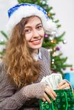 Attractive young Caucasian woman taking dollars cash in hands from green bag at Christmas eve Stock Photo