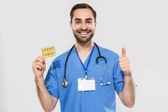 Attractive young cheerful male doctor wearing unifrom