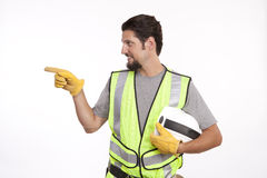 Attractive young construction worker pointing against white Stock Photography