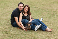 Attractive Young Couple. Attractive young multicultural couple with cute dog in a affectionate pose outdoors in a park setting Stock Images