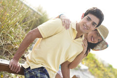Attractive young couple. An attractive young couple resting together against a wooden rail Stock Images
