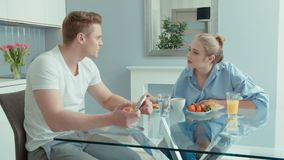 Attractive young couple arguing in the kitchen. Beautiful blonde caucasian woman having healhy breakfast at home. Young couple sitting at a table arguing stock video footage