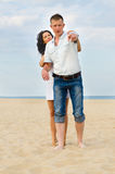 Attractive young couple on a beach. With the men pointing out something to his wife who is hugging him from behind Royalty Free Stock Image