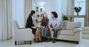 Attractive young couple and a beautiful real estate agent woman have a meeting on a large spacious living after a. Discussion couple happy hugging each other stock footage