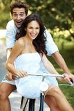 Attractive young couple on bike in a park Stock Photography