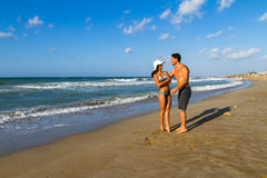 Attractive young couple in bikini and shorts at Royalty Free Stock Photos