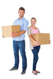 Attractive young couple carrying moving boxes Stock Images
