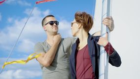 Attractive young couple chilling together on a yacht enjoying bright hot sunny day on vacation sailing the sea. The last days of summer, hot day, beautiful stock footage