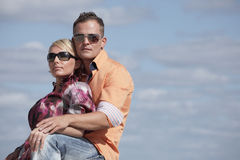 Attractive young couple on a cloudy sky background Stock Photography