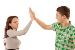 Attractive young couple congratulating themselves. With a high fives gesture as they slap each other on the hand, isolated on white Royalty Free Stock Photography