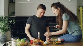 Attractive young couple cooking and chatting happily in the kitchen at home. Man cutting vegetables for salad and his. Attractive young couple cooking and have stock video