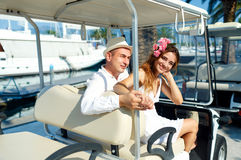 Attractive young couple driving electric car on a luxury waterfr Royalty Free Stock Image