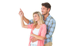 Attractive young couple embracing and pointing Stock Images