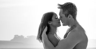 Attractive young couple enjoying a romantic kiss stock photography