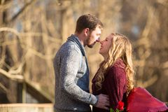 Attractive young couple facing each other. Looking into each others eyes smiling about to rub noses she is holding red balloon and red rose Royalty Free Stock Photo