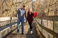 Attractive young couple facing each other on walkway. Attractive young couple facing each other looking into each others eyes she is smiling laughing holding red Stock Images
