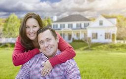 Attractive Young Couple In Front of Beautiful Home Stock Photo