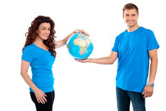 Attractive young couple holding a globe together. Isolated on white background Royalty Free Stock Photo