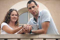 Attractive young couple holding hands on balcony. As if on honeymoon or getting engaged. shot on overcast day providing soft lighting Stock Photo