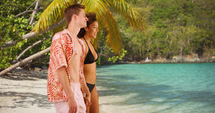 Attractive young couple holding hands on tropical beach. Stock Photography