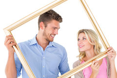Attractive young couple holding picture frame Stock Photos
