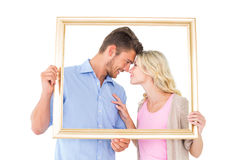 Attractive young couple holding picture frame Stock Photo