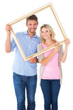 Attractive young couple holding picture frame Royalty Free Stock Image